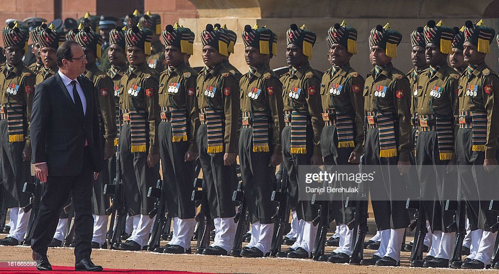 French President Francois Hollande observes the guard of honor during his welcoming reception at Rashtrapati Bhavan, the Presidential Palace on February 14, 2013 in New Delhi, India. French President Francois Hollande arrived in India on Thursday for a two-day trip, his first to Asia since becoming President last year and hopes to build the way for important trade contracts.