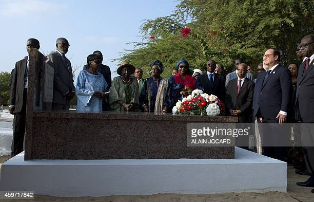 French President Francois Hollande pays his respects after laying a wreath on the former Senegalese President Leopold Sedar Senghor's grave at Bel...