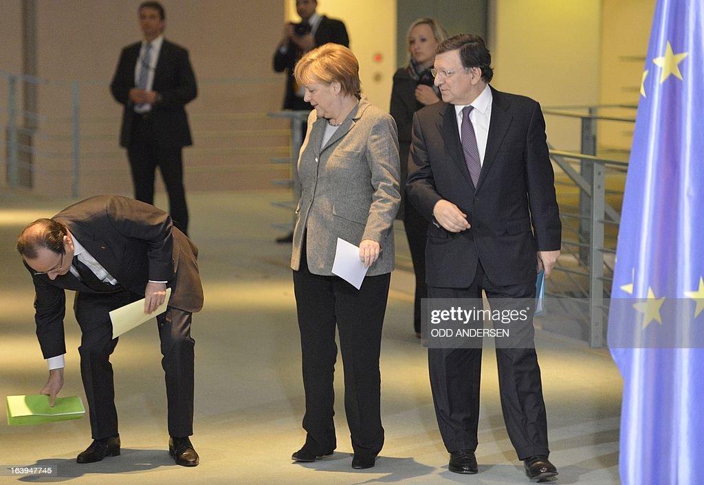 French President Francois Hollande (L) picks up his fallen papers as he arrives with German Chancellor Angela Merkel (C) and European Commission head Jose Manuel Barroso (R) to give a joint press conference at the Chancellery in Berlin on March 18, 2013 before a meeting with representatives of the European Round Table of Industrialists. ANDERSEN
