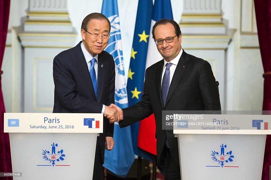 French President Francois Hollande (R) poses as he shakes hands with the UN Secretary-General following a joint press conference and a meeting on June 25, 2016 at the Elysee Palace in Paris. / AFP / GEOFFROY
