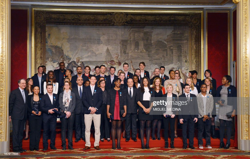 French President Francois Hollande (C) poses flanked by French medalists at the 2012 London olympics games, before he awards them with the French Legion d'Honneur during a ceremony on March 1, 2013 at the Elysee palace in Paris.