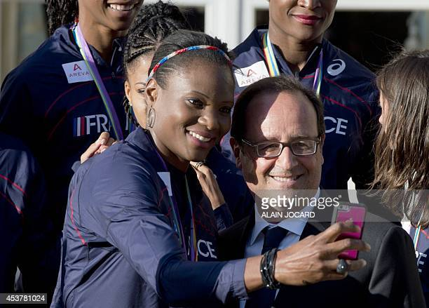 French President Francois Hollande poses for selfie with French athlete Muriel Hurtis during a family picture with the French athletes coming back...