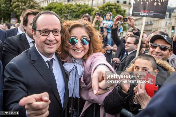 French President Francois Hollande poses with a French Armenian during a ceremony marking the 102nd anniversary of the Armenian genocide in Paris on...