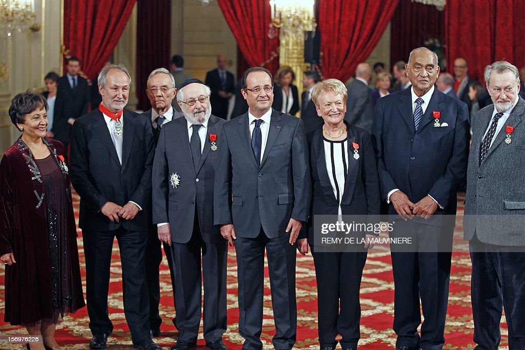 French President Francois Hollande (C) poses with awarded people at the end of an award ceremony on November 26, 2012 at the Elysee Palace in Paris. AFP PHOTO POOL REMY DE LA MAUVINIERE Tunisian journalist Souhayr Belhassen, former chairman of Arte channel, Jerome Clement, member of Science Academy Pierre Joliot, Alain Goldman, the grand rabbi of Paris, French President Francois Hollande, French general counsellor Marie-Thérèse Delrieu, former Mayotte deputy Henry Jean-Baptiste and Bernard Faivre d'Arcier.