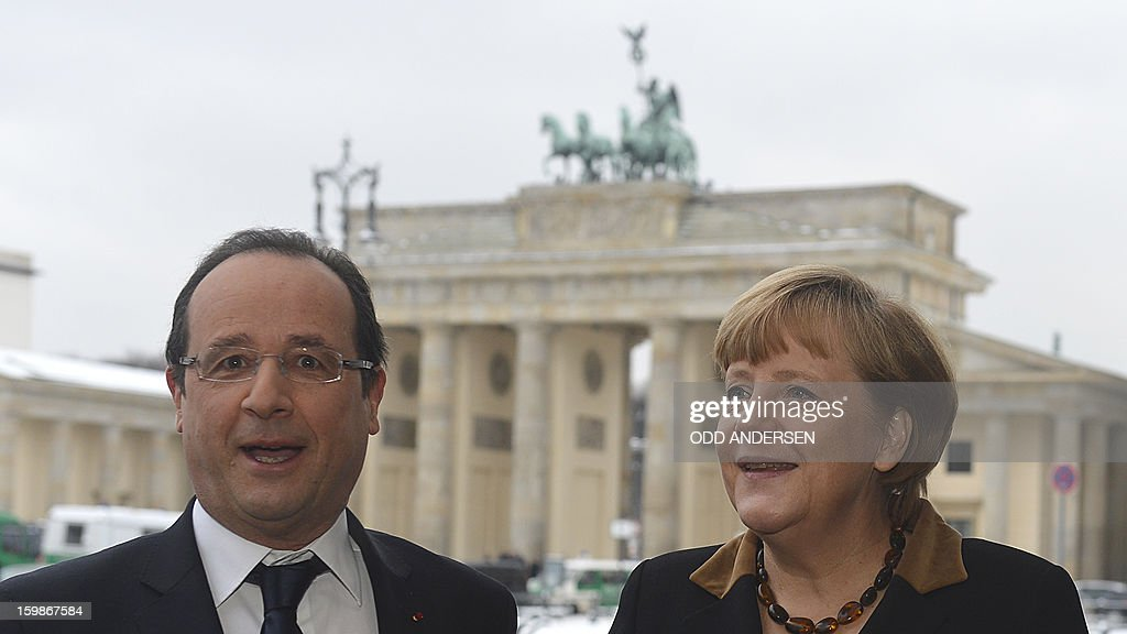 French President Francois Hollande (L) poses with German Chancellor Angela Merkel in front of the Brandenburg Gate as they arrive at the French Embassy in Berlin on January 22, 2013 for a meeting as part of the celebration to mark 50 years since the Elysee Treaty launched after WWII the French-German cooperation. Hollande is to meet there with Angela Merkel. In signing the landmark treaty on January 22, 1963, then French president Charles de Gaulle and West German chancellor Konrad Adenauer sealed a new era of reconciliation between the former foes which has since driven European unity.