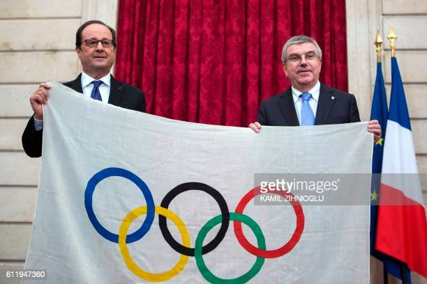 French President Francois Hollande poses with International Olympic Committee President Thomas Bach after Bach received an Olympic flag from the 1924...