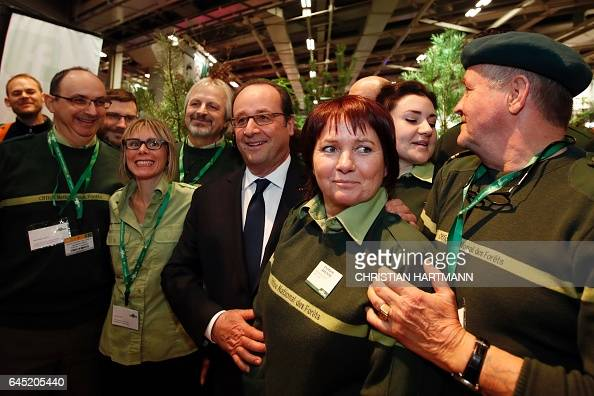 French President Francois Hollande poses with representatives of the National Forestry Office as he visits the International Agricultural fair in...