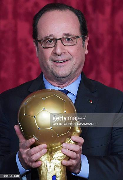 French President Francois Hollande poses with the IHF International Handball Federation Men's World Championship 2017 trophy during a ceremony at the...