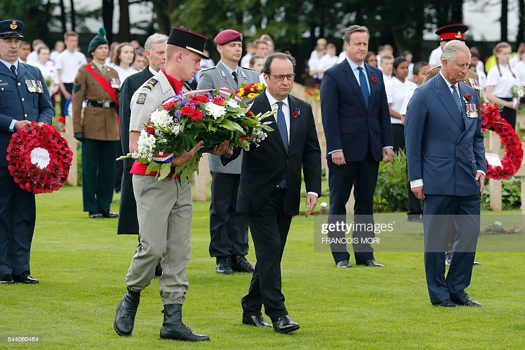 French President Francois Hollande (L) prepares to lay a spray of flowers as British Prime Minister David Cameron (back R) and Britain's Prince Charles (front R) walk next to him as they attend the memorial ceremony on July 1, 2016 at the Thiepval Memorial, in Thiepval, during which Britain and France will mark the 100 years since soldiers emerged from their trenches to begin one of the bloodiest battles of World War I (WWI) at the River Somme. Under grey skies, unlike the clear sunny day that saw the biggest slaughter in British military history a century ago, the commemoration kicked off at the deep Lochnagar crater, created by the blast of mines placed under German positions two minutes before the attack began at 7:30 am on July 1, 1916. / AFP / POOL / Francois Mori