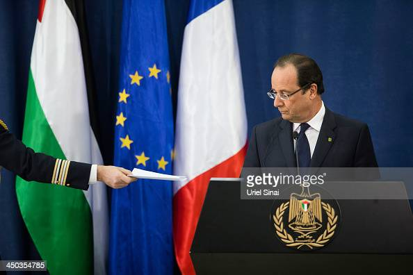 French President Francois Hollande receives a message from one of his aids during a joint press conference with Palestinian leader Mahmud Abbas on...