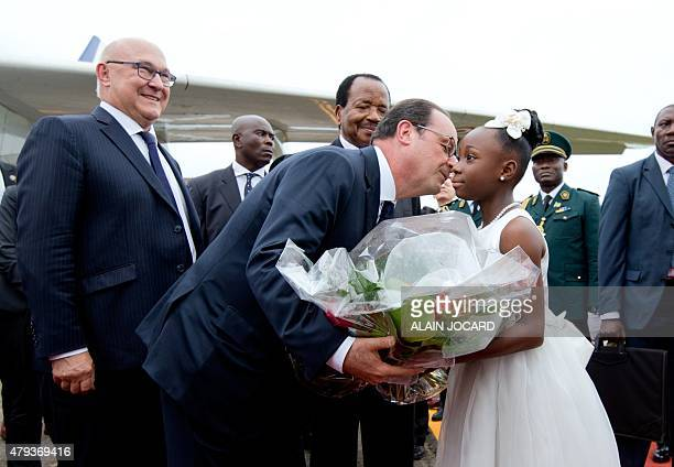 French President Francois Hollande receives flowers from a girl flanked by French Finance Minister Michel Sapin and Cameroon's President Paul Biya as...