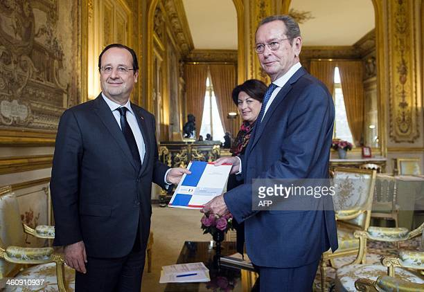 French President Francois Hollande receives the report on children's rights from rights defenders Dominique Baudis and Marie Derain during a meeting...