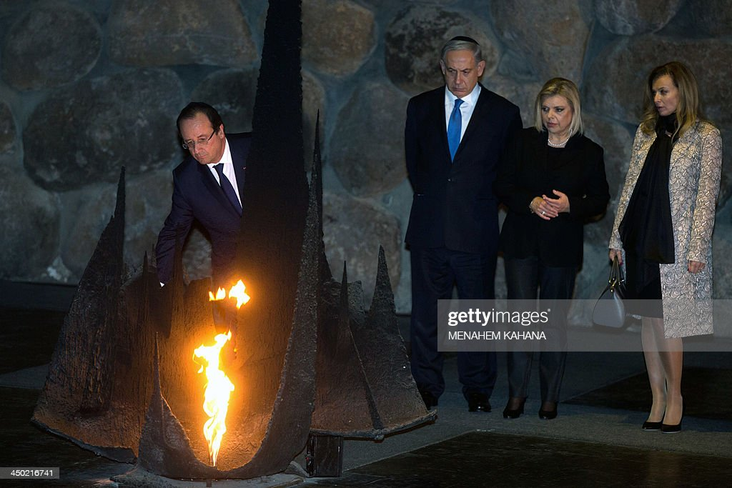 French President Francois Hollande rekindles the eternal flame at the Hall of Remembrance on November 17, 2013, during his visit to the Yad Vashem Holocaust Memorial museum in Jerusalem commemorating the six million Jews killed by the Nazis during World War II. In the background is Hollande's companion, Valerie Trierweiler (R), Israeli Prime Minister Benjamin Netanyahu and his wife Sara.