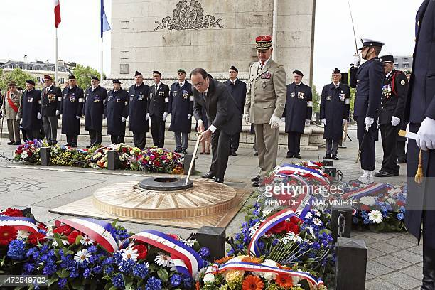 French President Francois Hollande rekindles the eternal flame at the Tomb of the Unknown Soldier a ceremony at the Arc de Triomphe in Paris on May 8...
