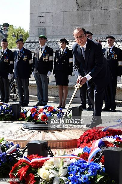 French President Francois Hollande rekindles the eternal flame at the Tomb of the Unknown Soldier at the base of the 'Arc de Triomphe' during a...