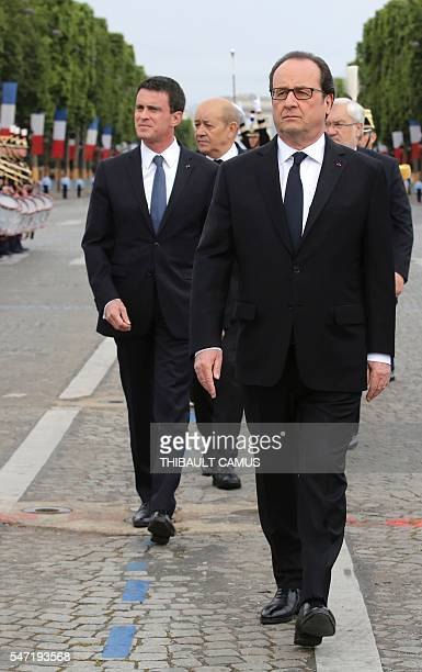 TOPSHOT French President Francois Hollande reviews the troops with Prime Minister Manuel Valls Defense Minister JeanYves le Drian and French junior...