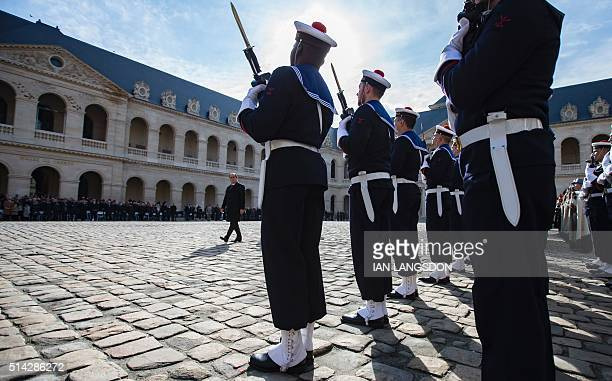 French President Francois Hollande reviews troops during an official funeral ceremony held for the late French politician Yves Guena at the Hotel des...