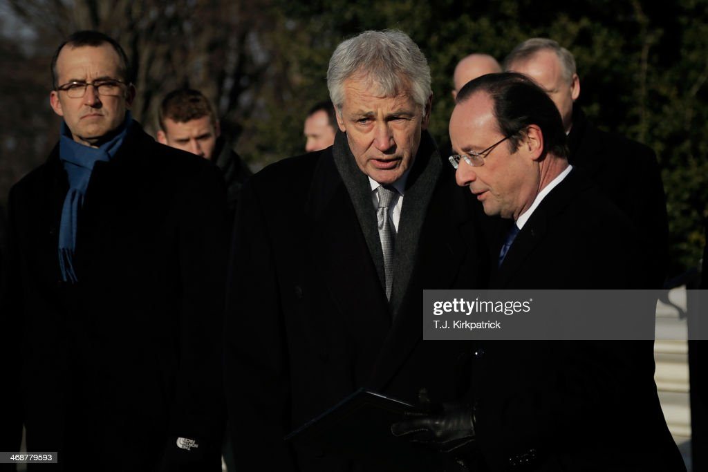 French President Francois Hollande, right, and U.S. Secretary of Defense <a gi-track='captionPersonalityLinkClicked' href=/galleries/search?phrase=Chuck+Hagel&family=editorial&specificpeople=504963 ng-click='$event.stopPropagation()'>Chuck Hagel</a>, center, leave after a wreath-laying ceremony at the Tomb of the Unknown Soldier on February 11, 2014 in Arlington, Virginia. 2014 marks the 70th anniversary of the Allied Forces D-Day landing in Normandy, which helped lead to the liberation of France and the European continent.