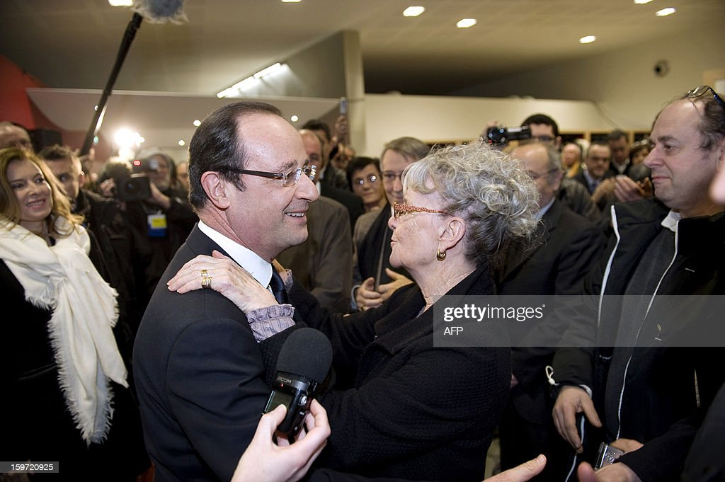 French President Francois Hollande (2ndL) salutes a woman as he arrives to attend the inauguration of a community hall in Auzelou a Tulle, Correze region central France on January 19, 2013.