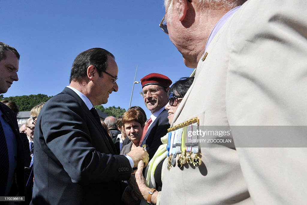French President Francois Hollande (L) shakes a woman's hand during a ceremony in Tulle, central France, on June 9, 2013, to commemorate the Nazi massacre of Tulle in 1944. AFP PHOTO / POOL / THIERRY ZOCCOLAN