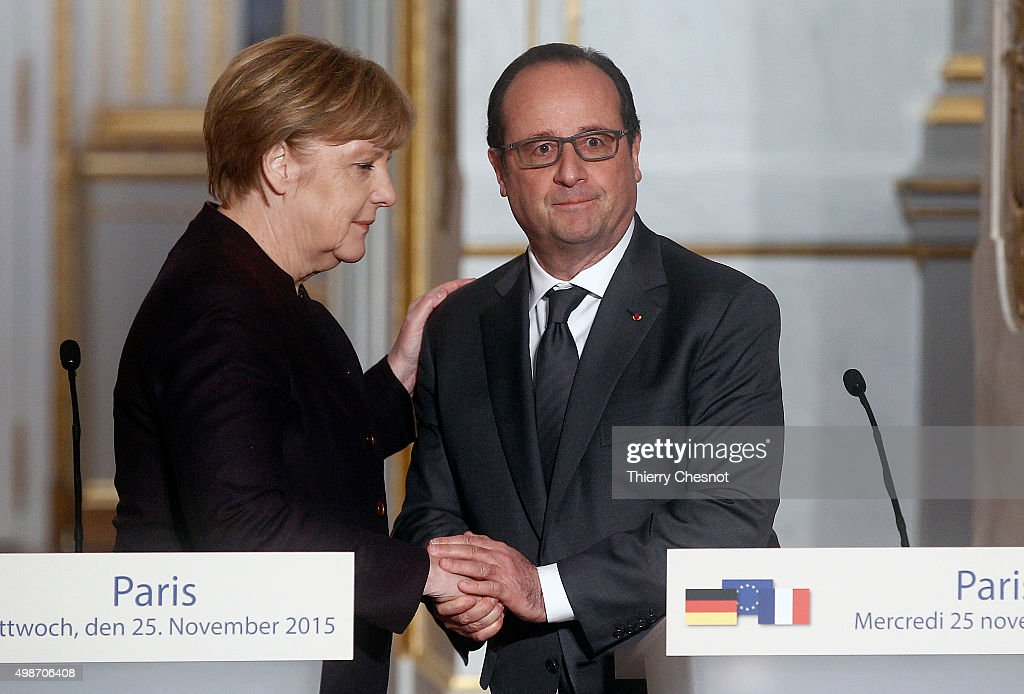 French President Francois Hollande shakes hand with German Chancellor Angela Merkel after a press conference at the Elysee Presidential Palace on...