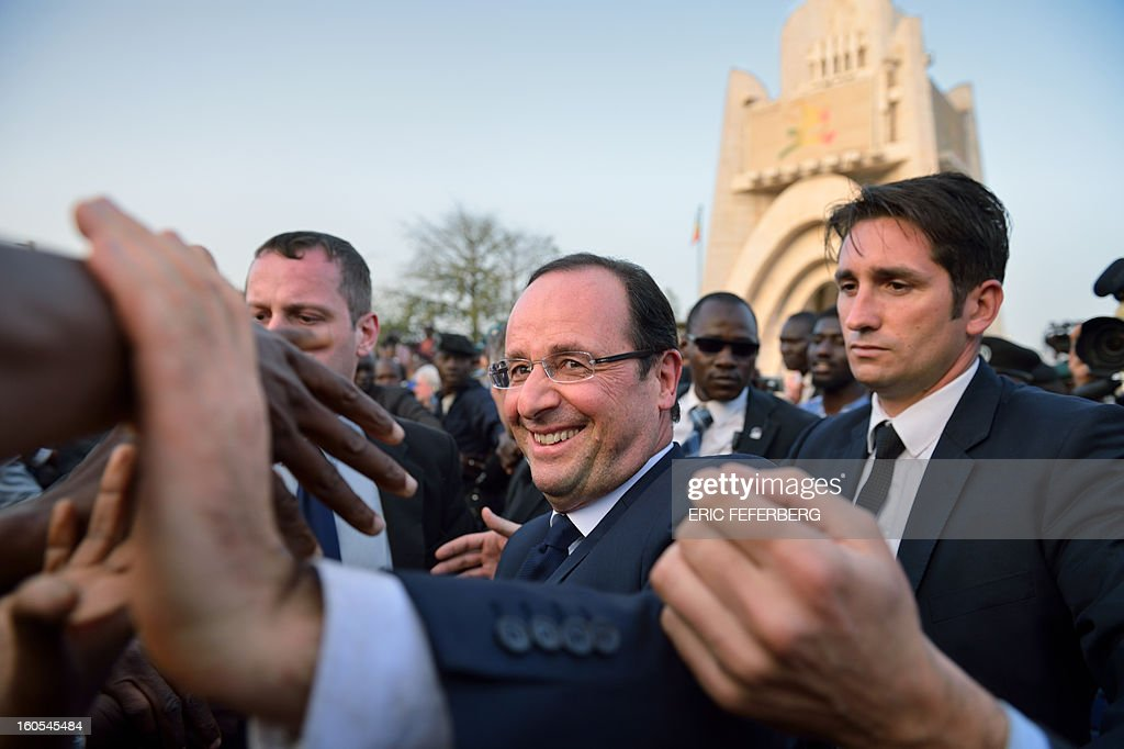 French President Francois Hollande (C) shakes hands to people amongst the crowd on February 2, 2013 after delivering a speech with his Malian counterpart at the Independence Square in Bamako. French President Francois Hollande called on Africans to take over the fight against extremism as he received a rapturous welcome today in Mali, where a French-led offensive has driven back Islamist rebels from the north.