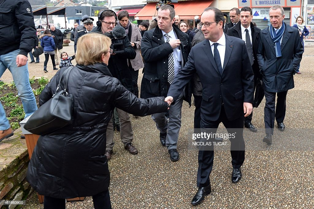 French President Francois Hollande shakes hands with a woman as he visits a market in Tulle on January 17 2015 Hollande stressed that France had...