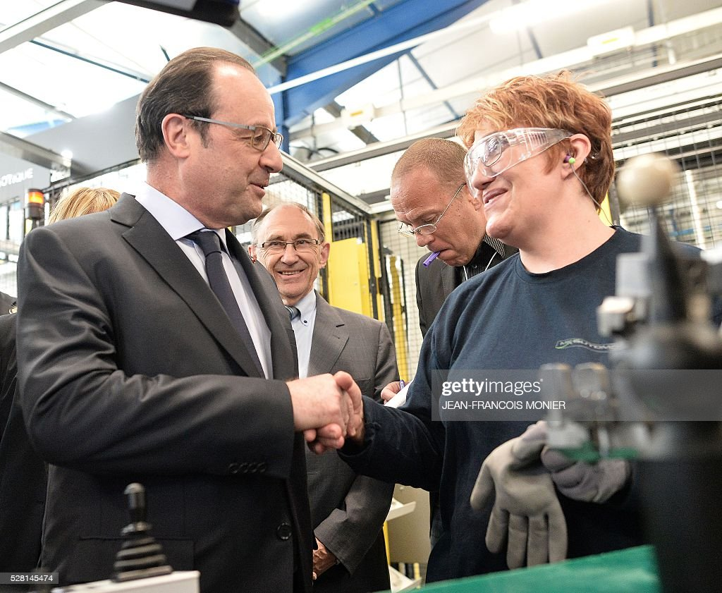 French President Francois Hollande (L) shakes hands with a worker during a visit at the MK Automotive Mecachrome plant on May 4, 2016 in Sable-sur-Sarthe, northwestern France. / AFP / JEAN