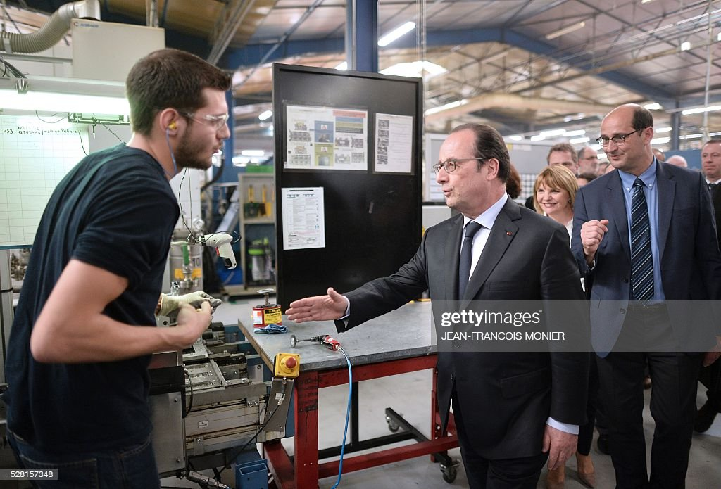 French President Francois Hollande (C) shakes hands with a worker during a visit at the MK Automotive Mecachrome plant on May 4, 2016 in Sable-sur-Sarthe, northwestern France. / AFP / JEAN