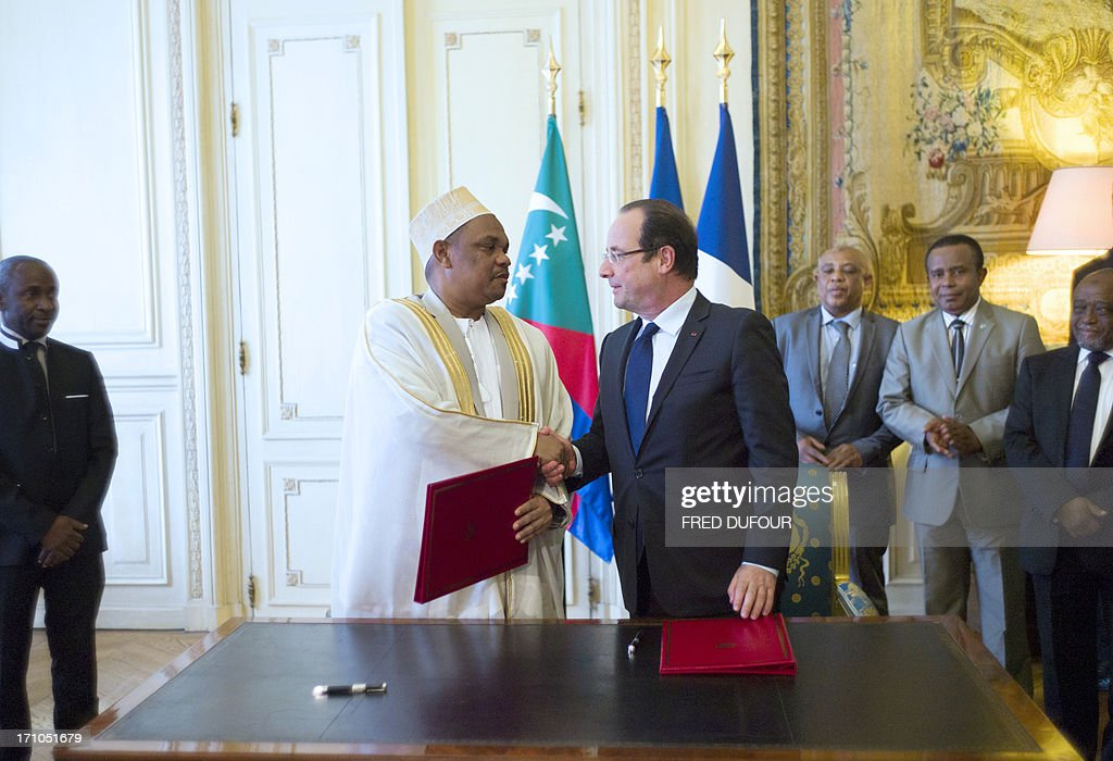 French president Francois Hollande (front R) shakes hands with Comoros' president Ikililou Dhoinine (front L) after signing an agreement after a meeting at the Elysee palace in Paris, on June 21, 2013.