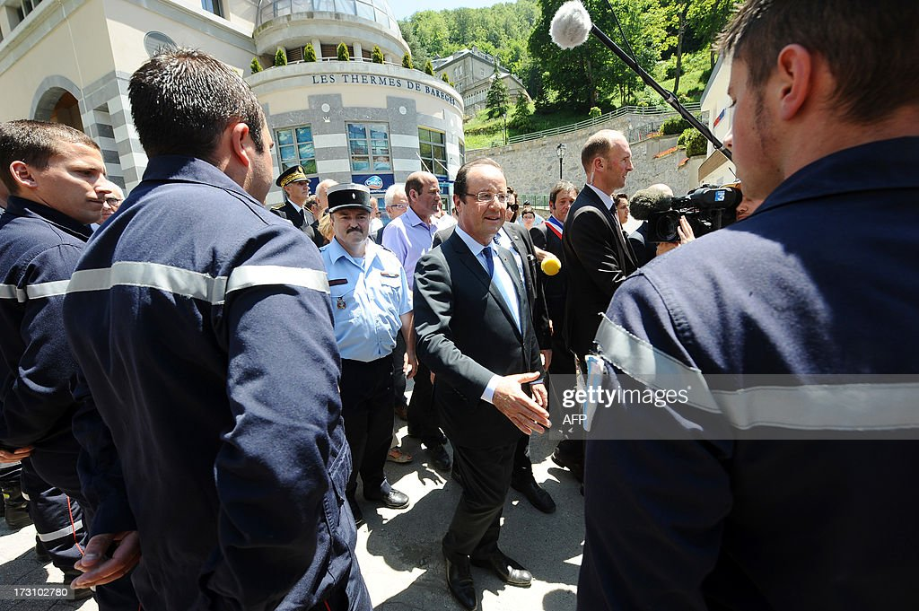 French President Francois Hollande shakes hands with firemen on July 7, 2013 as he visits the village of Bareges, southwestern France, hit by flash floods in June 2013. Hollande arrived earlier in Tarbes for a visit to damaged villages of Bagneres-de-Luchon and Bareges hit by floods the past month.