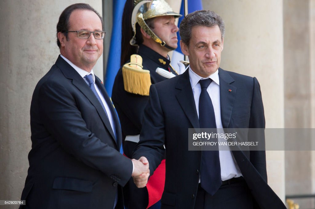 French President Francois Hollande (L) shakes hands with former French president and and head of the right-wing opposition party 'Les Republicains' (The Republicans) Nicolas Sarkozy (R) prior to attend a meeting with French leaders of political parties and movements after Britain voted to leave the European Union the day before, on June 25, 2016 at the Elysee presidential Palace in Paris. As the 'Brexit' vote sent global financial markets into freefall, Moody's cut Britain's credit rating outlook to 'negative', saying the vote to pull out of the European Union could hurt its economic prospects. / AFP / GEOFFROY