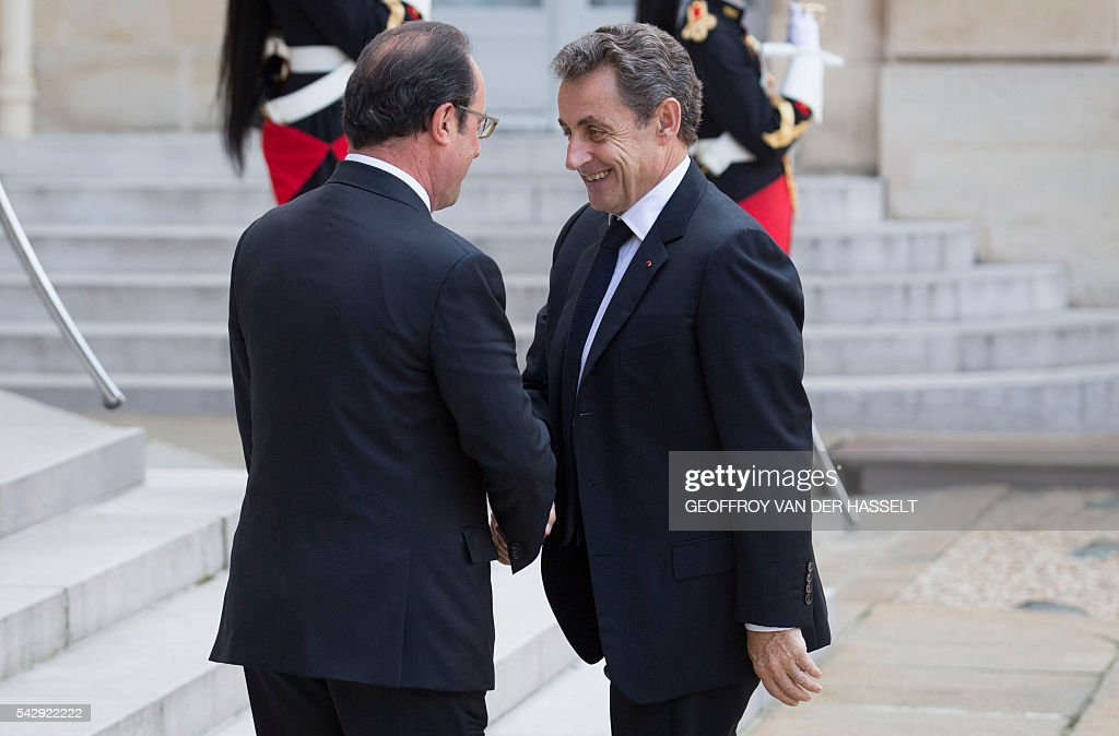 French President Francois Hollande (L) shakes hands with former French president and head of the right-wing opposition party 'Les Republicains' (The Republicans) Nicolas Sarkozy (R) prior to attend a meeting with French leaders of political parties and movements after Britain voted to leave the European Union the day before, on June 25, 2016 at the Elysee presidential Palace in Paris. As the 'Brexit' vote sent global financial markets into freefall, Moody's cut Britain's credit rating outlook to 'negative', saying the vote to pull out of the European Union could hurt its economic prospects. / AFP / GEOFFROY