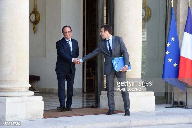 French President Francois Hollande shakes hands with French Economy and Industry Minister Emmanuel Macron following the last weekly cabinet meeting...