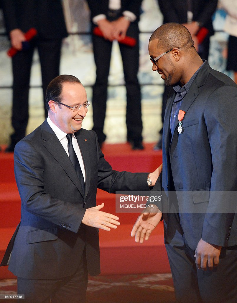 French President Francois Hollande (L) shakes hands with French judoka Teddy Riner, gold medalist at the 2012 London olympics games, after his award with the French Legion d'Honneur during a ceremony on March 1, 2013 in Paris. AFP PHOTO / POOL / MIGUEL MEDINA