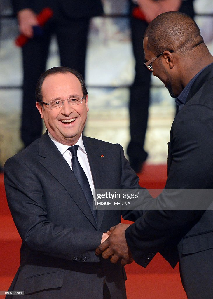 French President Francois Hollande (L) shakes hands with French judoka Teddy Riner, gold medalist at the 2012 London olympics games, after his award with the French Legion d'Honneur during a ceremony on March 1, 2013 in Paris.