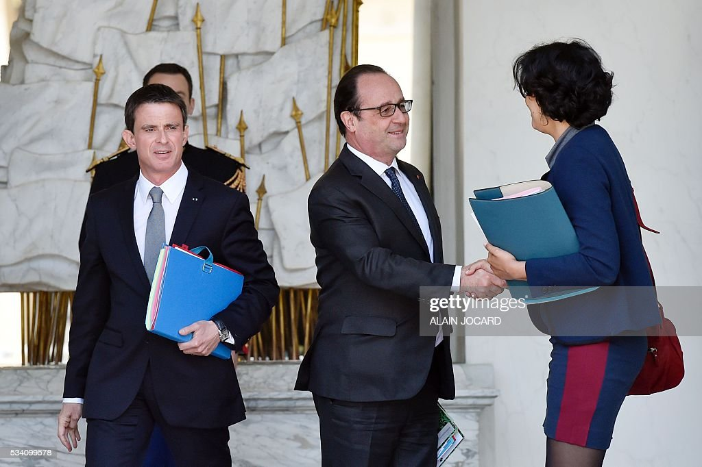 French president Francois Hollande (C) shakes hands with French Labour minister Myriam El Khomri (R), next to French Prime Minister Manuel Valls (L), after the weekly cabinet meeting on May 25, 2016, in Paris, at the Elysee presidential palace. / AFP / ALAIN