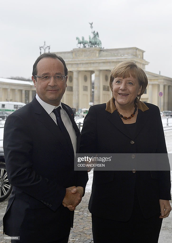 French President Francois Hollande (L) shakes hands with German Chancellor Angela Merkel as they pose in front of the Brandenburg Gate as they arrive at the French Embassy in Berlin on January 22, 2013 for a meeting as part of the celebration to mark 50 years since the Elysee Treaty launched after WWII the French-German cooperation. Hollande is to meet there with Angela Merkel. In signing the landmark treaty on January 22, 1963, then French president Charles de Gaulle and West German chancellor Konrad Adenauer sealed a new era of reconciliation between the former foes which has since driven European unity.