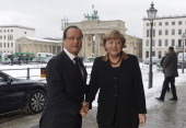French President Francois Hollande shakes hands with German Chancellor Angela Merkel as they pose in front of the Brandenburg Gate as they arrive at...