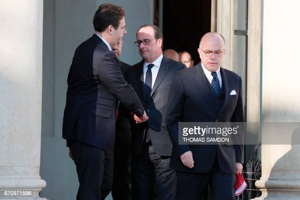 French President Francois Hollande shakes hands with Interior Minister Matthias Fekl next to Prime Minister Bernard Cazeneuve after a meeting of the...
