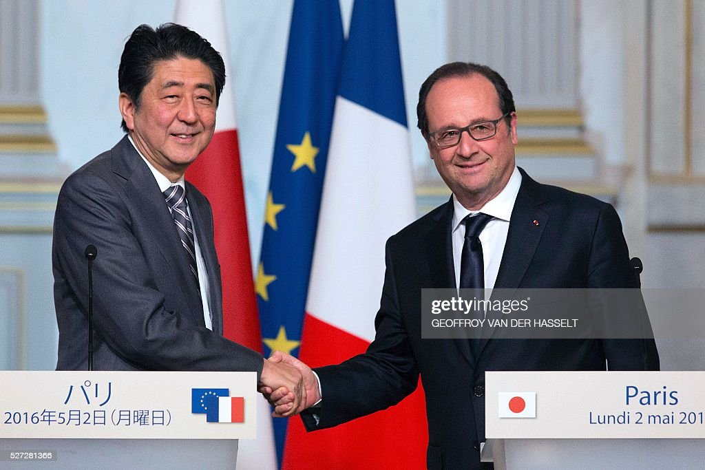 French President Francois Hollande (R) shakes hands with Japanese Prime Minister Shinzo Abe during a press conference in Paris on May 2, 2016. / AFP / GEOFFROY
