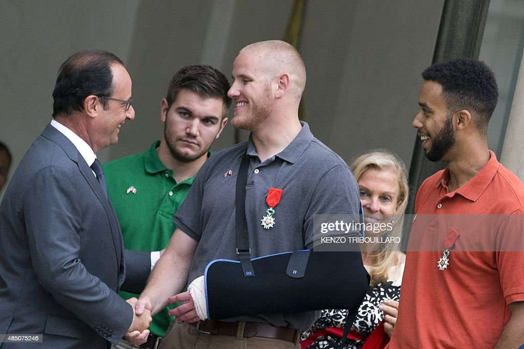 French President Francois Hollande shakes hands with offduty US serviceman Spencer Stone next to offduty serviceman Alek Skarlatos and Anthony Sadler...