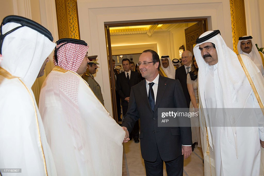 French President Francois Hollande (C) shakes hands with officials after being greeted by Qatari Emir Sheikh Hamad bin Khalifa al-Thani (R) at the Emiri Diwan in Doha on June 23, 2013. Hollande is on a two-day official visit to Qatar for talks on the Syrian civil war and on economic ties with the gas-rich Gulf state. AFP PHOTO/BERTRAND LANGLOIS