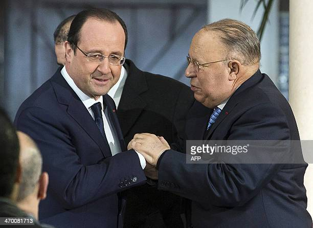 French President Francois Hollande shakes hands with Paris Mosque rector Dalil Boubakeur after delivering speeches at the 'Grande Mosquee de Paris'...