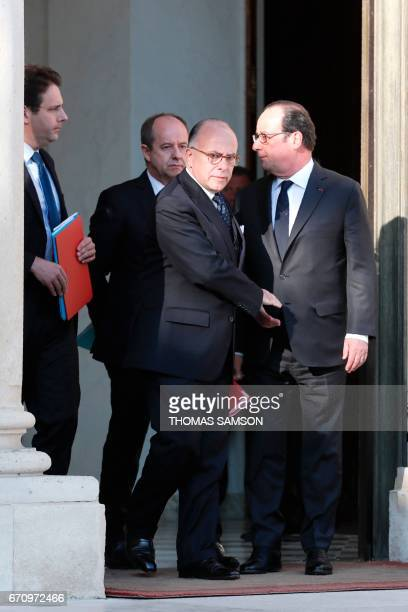 French President Francois Hollande shakes hands with Prime Minister Bernard Cazeneuve after a meeting of the Defense Council on April 21 2017 at the...
