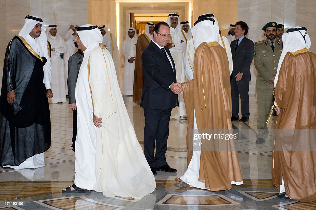 French President Francois Hollande (C) shakes hands with Qatari officials at the Emiri Diwan in Doha on June 23, 2013. Hollande is on a two-day official visit to Qatar for talks on the Syrian civil war and on economic ties with the gas-rich Gulf state.