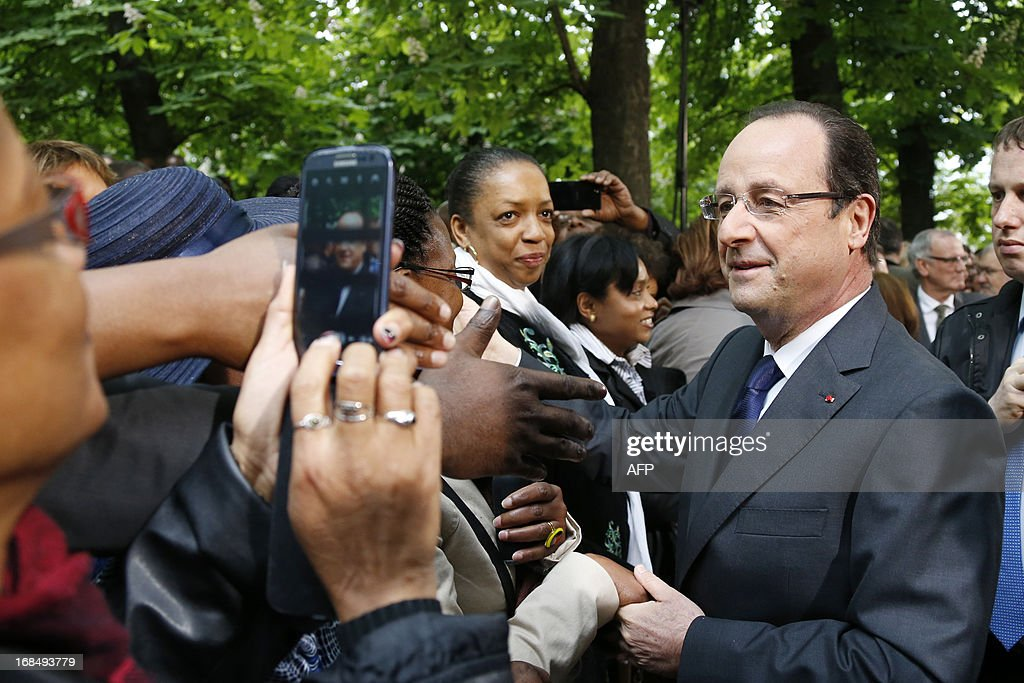 French President Francois Hollande (R) shakes hands with supporters after a ceremony at the Luxembourg Gardens to mark the abolition of slavery and to pay tribute to the victims of the slave trade in Paris May 10, 2013.