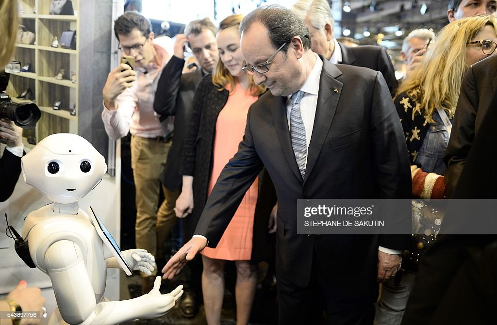 French President Francois Hollande (C) shakes hands with the IBM Watson powered robot during his visit to the Viva technology event in Paris on June 30, 2016. / AFP / POOL / STEPHANE
