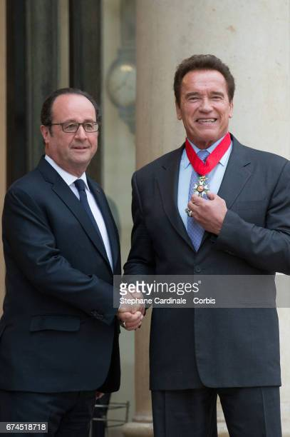 French President Francois Hollande shakes hands with US actor and former governor of California Arnold Schwarzenegger after he was awarded France's...