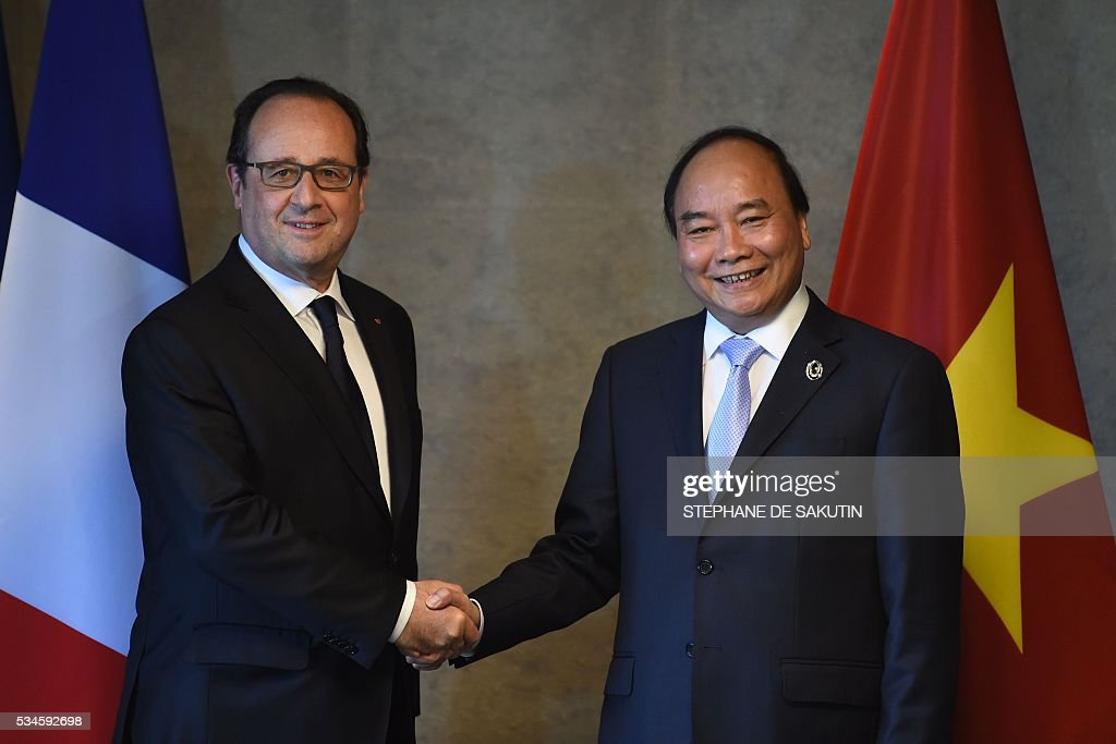 French President Francois Hollande (L) shakes hands with Vietnam's Prime Minister Nguyen Xuan Phuc during their bilateral meeting on the sidelines of the second day of the G7 Summit in Shima in Mie prefecture on May 27, 2016. A British secession from the European Union in next month's referendum could have disastrous economic consequences, G7 leaders warned on May 27 at the close of the summit in Japan. / AFP / STEPHANE